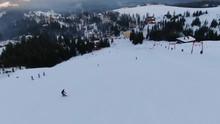 "Постер, картина, фотообои ""A long snowy slope down the mountain with lots of people skiing and snowboarding, beautiful resort down the hill, aerial shot"""