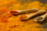 Spices and herbs on a dark background. Paprika, curcuma, chili pepper, parsley, basil, oregano. Cooking and healthy eating concept, selective focus