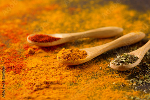 Spices and herbs on a dark background. Paprika, curcuma, chili pepper, parsley, basil, oregano. Cooking and healthy eating concept, selective focus © Iuliia Metkalova