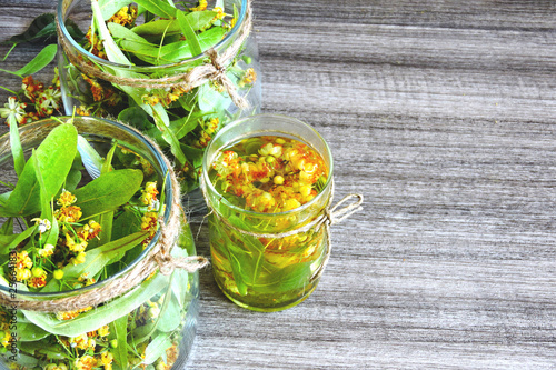Linden flowers in a glass jar. Harvesting of linden tea. Linden tea. Healing herbal tea. © Oksana
