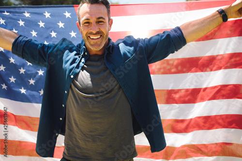 fototapeta na ścianę Happy man standing outdoors holding american flag