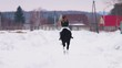 Winter time. A woman riding a horse in a village