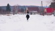 Winter time. A woman riding a horse in a village. Back view