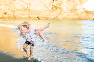 A couple having fun at the beach by the ocean