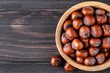 Filtered image of Hazelnuts in a wooden bowl on rustic background,top view.
