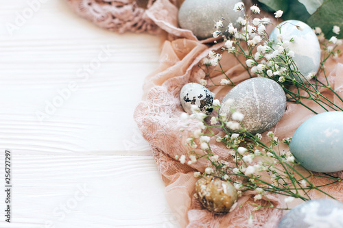Stylish Easter eggs on rustic fabric with spring flowers and eucalyptus branch on white wooden background. Space for text. Modern pastel eggs painted with natural dye. Happy Easter greetings - 256727297
