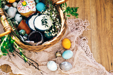 Stylish Easter eggs, easter bread cake, ham, beets, sausage, butter, green branches in wicker basket on rustic fabric with spring flowers. Happy Easter, holiday traditional feast