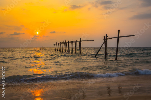 fototapeta na ścianę The old and broken wooden bridge on the beach with sunset