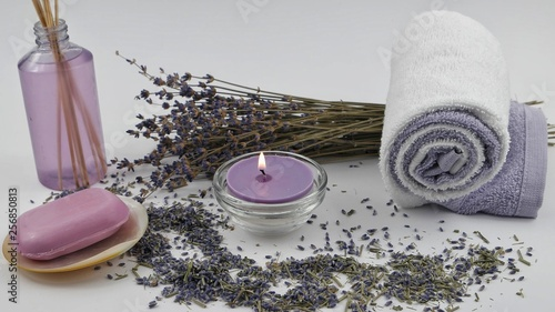 Burning aromatic candles, dry lavender, cosmetics on the white background. Spa and aromatherapy accessories. © botevvs