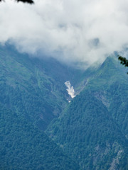 High green mountains with snow in the gorges. The tops of the mountains in the clouds and fog. © Дмитрий Поташкин