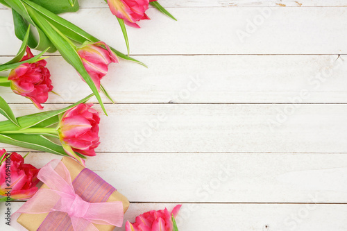 Leinwandbild Motiv Side border of pink flowers with gift box against a rustic white wood background