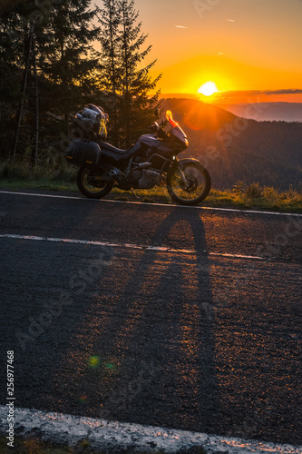 Adventure motorcycle, silhouette touristic motorbike. the mountain peaks in the sunset. Copy space. Concept of Tourism, adventures, active lifestyle, Transfagarasan, Romania, vertical photo