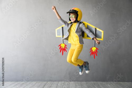 Leinwandbild Motiv Happy child playing with toy jetpack