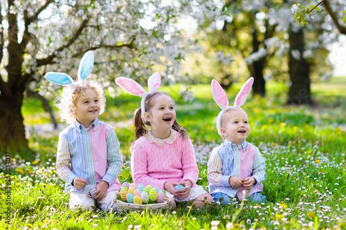 Leinwandbild Motiv Easter egg hunt. Kids with bunny ears and basket.