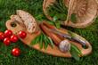 Bärlauch, frisch geerntet auf Holzbrett liegend mit Tomaten, Wurst und Brot, Picknick auf Wiese