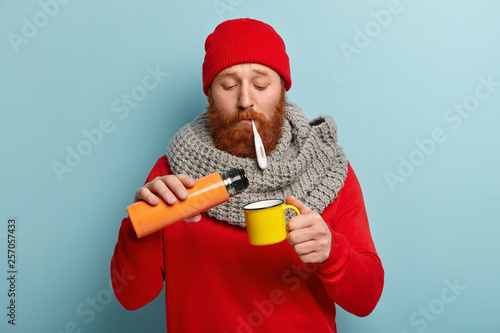 Sad bearded red haired young man measures temperature, pours tea from thermos bottle, wears warm winter clothes, being fed up of seasonal disease, isolated on blue background. Illness concept