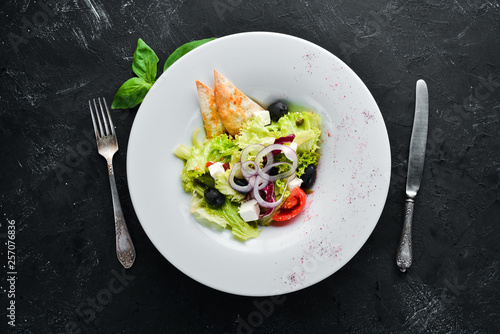 Leinwandbild Motiv Greek salad. Vegetable salad with feta cheese, olives and cherry tomatoes. In the plate. Top view. Free space for your text. Rustic style.
