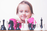 Humorous photo of little champion. Beautiful child girl learns to play chess. Development, childhood, success, wunderkind concept