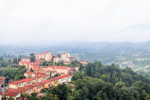 Chiusi village cityscape in Tuscany Italy with orange red rooftop tile houses on mountain countryside and rolling hills with morning mist haze fog