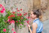 Monticchiello, Italy town or village city in Tuscany closeup of woman young girl smelling touching red flower pots decorations on summer day stone wall architecture