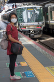 a woman with a mask on her face, standing on a platform of a railway station waiting for a train, Japan.