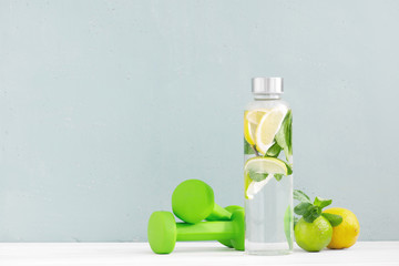 Water with lemon and mint in the glass bottle and green dumbbells