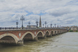 Pont de Pierre and Basilica of St. Michael with its tower under clouds, in Bordeaux, France