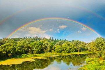 Bright double rainbow in the sky with clouds above the forest and the river
