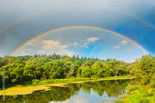 Bright double rainbow in the sky with clouds above the forest and the river © E.O.