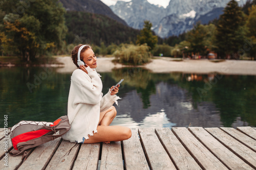 Leinwandbild Motiv Attractive young woman listening to music via wifi headphones and smartphone on the lake