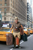 Tourist in a hat with a bunch of suitcases