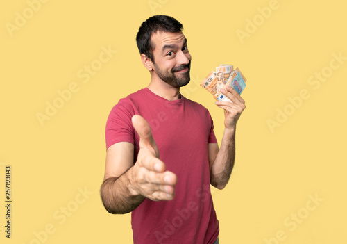 Leinwanddruck Bild Man taking a lot of money shaking hands for closing a good deal on isolated yellow background
