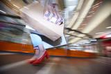 Zbliżenie: moda nie do poznania dziewczyna nosi pomarańczowe buty, niosąc papier pozbawiony torby na zakupy w centrum handlowym, niewyraźne efekt