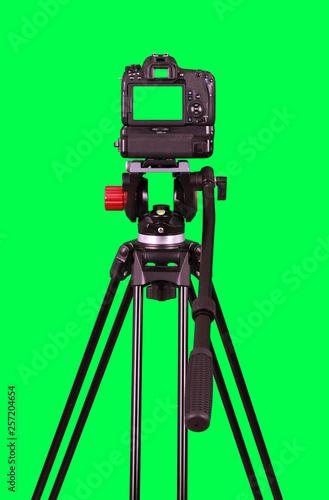 Dslr camera with green screen on the tripod isolated on green background. The chromakey. Green screen. - 257204654