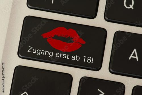 Ein Comuter und eine Taste mit dem Hinweis auf eine Pornoseite mit Zugang ab 18 - 257245207