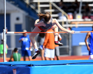 Young teenage girl competing in the high jump at a high school track meet