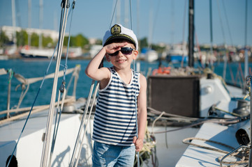 cute happy caucasian kid in captain cap and sunglasses on yacht board in summer sea port