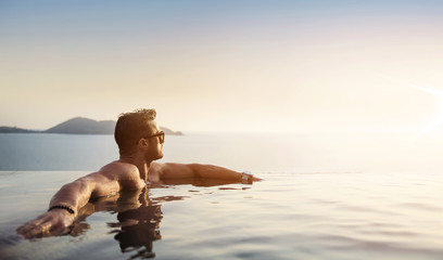 Portrait of a muscualar man relaxing in a tropical, hot water