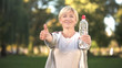 Leinwandbild Motiv Middle-aged woman showing bottle of water and thumbs up, healthy lifestyle