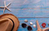 From above summer hat near sunglasses and sea stars with seashells on blue wooden background - 257342454