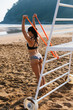 Leinwandbild Motiv Fit young woman in bikini exercising at the beach with resistande band. Summer healthy outdoor fitness workout.