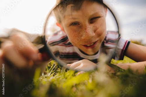 Leinwandbild Motiv Boy looking through magnifying glass