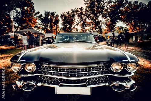 Leinwandbild Motiv Close-up wide-angled photo of black vintage retro car with shining chrome radiator grille, bumper and headlamps