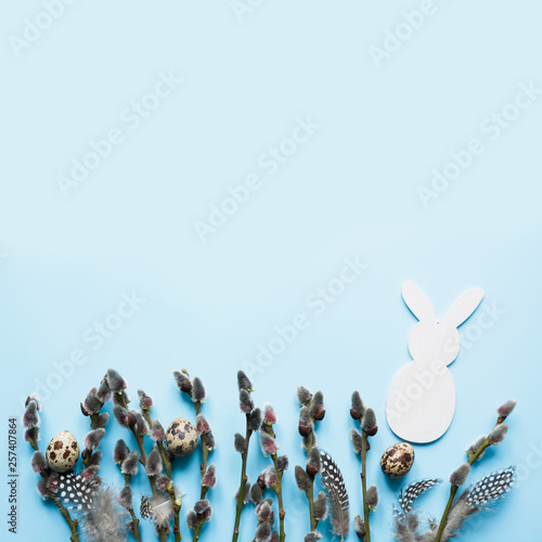 Easter creative frame of willow branch on blue background. Copy space, top view. - 257407864
