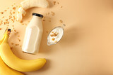 Composition with bottle of banana smoothie on color background