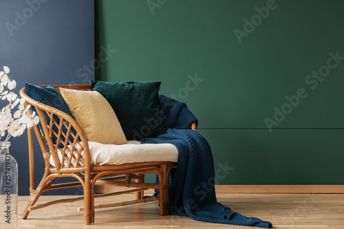 Blanket and pillows on rattan sofa in green and blue living room interior with flowers. Real photo