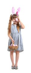 Cute little girl with Easter eggs and bunny ears on white background © Leonid