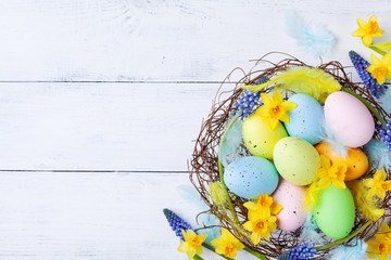 Сolorful Easter eggs in nest, feather and spring flowers on white table top view. Holiday card or banner.