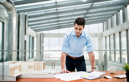 Young businessman or architect with model of a house standing in office, working. - 257446228