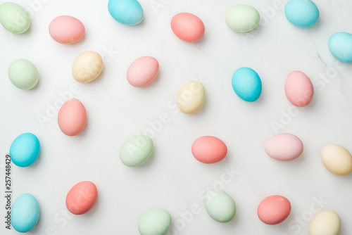 Leinwanddruck Bild background with colorful pastel easter eggs on white